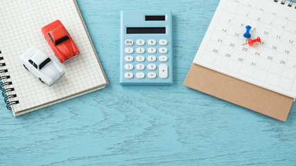Calculator and toy cars on wooden background