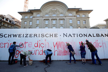 Members of the sovereign money initiative, a referendum campaign that would abolish traditional bank lending and allow only money created by the central bank, clean up after spraying a slogan on the Swiss National Bank (SNB) in Bern