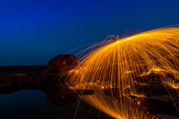 Swing fire dancing show.Swirl Steel Wool light Photography over the rock and water at night Sam Phan Bok.Photo by long exposure with noise and grain.