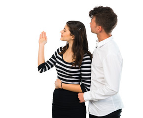 Young couple pointing back with the index finger on isolated white background