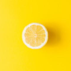 Lemon on vivid yellow background. Minimal summer concept. Flat lay.