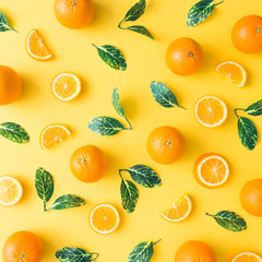 Creative summer pattern made of oranges and green leaves on pastel yellow background. Fruit minimal...