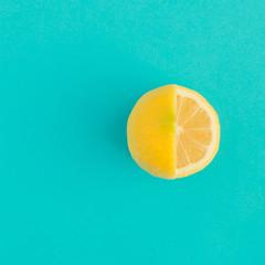 Yellow lemon fruit on bright blue background. Minimal flat lay concept.