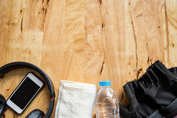 Fitness concept with bottle of water, mobile phone and earphones, towel , fitness glove over wooden background.