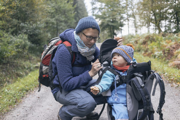 Son eating bread, sitting in his back-basket, next to his mother during hiking