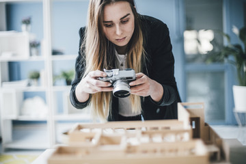 Architect taking photo of architectural model in office