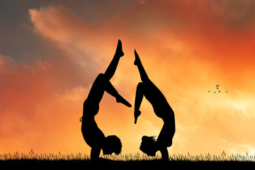 couple yoga together at sunset
