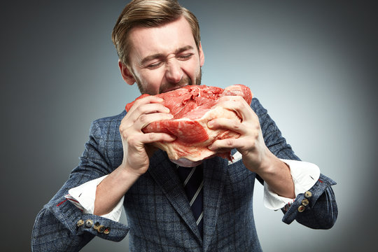 A man in a business suit with a piece of raw meat.