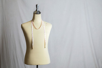 Pins on Mannequin with measuring line on white background.