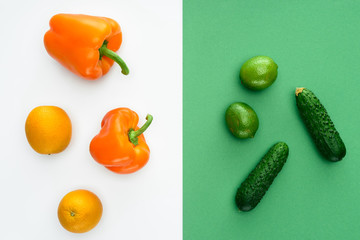 top view of orange and green fruits and vegetables on white and green surface