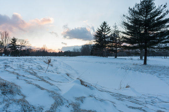 A sandpit at a golf course covered in snow, and the sun setting in the distance. It is now called Acacia metropark.
