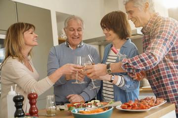 Senior people cheering with wine while preparing meal