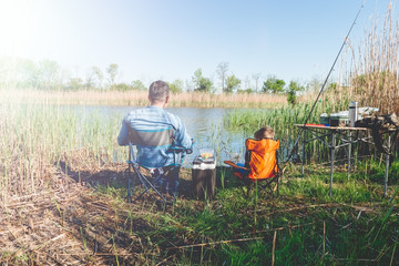 Father and son relaxed, fishing on the lake on the sun