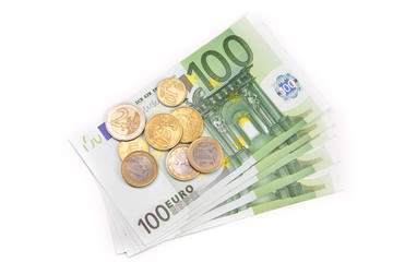 Stack of Euro banknotes and coins isolated. 100 Euro banknotes. European currency money banknotes isolated on white backdrop. Top view closeup. Salary, savings, european union economic crisis concept.