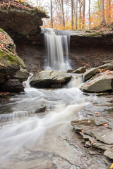 A rushing waterfall flowing through a rocky valley at Cuyahoga Valley National Park. It is autumn, and yellow leaves are scattered across the ground.