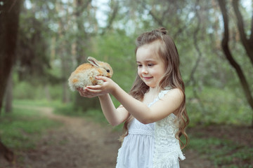 Little girl with small rabbit.