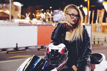 Portrait woman biker enjoying night city life and lights sitting