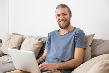 Portrait of young smiling man sitting on big gray sofa with laptop and joyfully looking in camera isolated