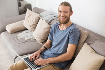 Portrait of young smiling man sitting on big gray sofa with laptop and happily looking in camera isolated