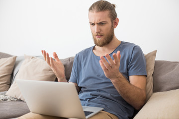 Portrait of young thoughtful man sitting on gray sofa and amazedly looking in  laptop at home