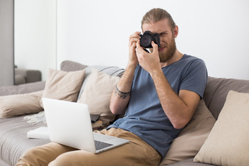 Portrait of young man sitting on gray sofa with laptop on knees and camera in hands at home isolated