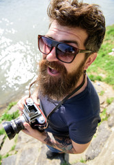 Reporter photographer concept. Man with beard and mustache wears sunglasses, water surface on background. Guy shooting nature near river or pond. Hipster on smiling face holds old fashioned camera.