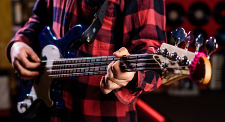 Male hands holds bass guitar, play music in club atmosphere background. Play guitar concept. Fingers clamp strings on bass guitar neck. Closeup of blurry male hands playing the guitar.