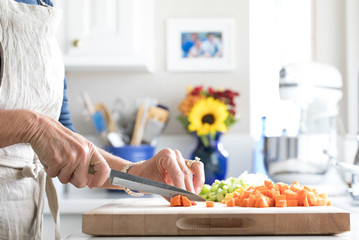 Photograph of a woman chopping vegetables on a cutting board in the kitchen