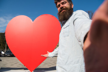 Hipster, tourist with long beard looking at camera, taking selfie photo. Man, with beard on cheerful face pointing at red heart sculpture, sky on background. Love symbol concept.