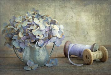 Textured photography of a dried hydrangea bloom in a pewter vase with wooden ribbon spools