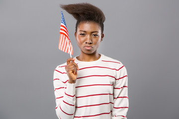 Multinational state. Confident young woman smiling while showing American flag to you