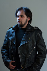 Rock or biker style. Portrait of a brutal guy with a beard in a black leather jacket.