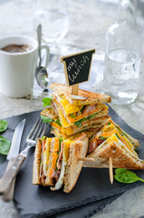 Delicious sandwich with ham, cheese, eggs, lettuce. High club sandwich with toast.