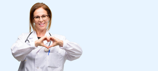 Doctor woman, medical professional happy showing love with hands in heart shape expressing healthy and marriage symbol isolated blue background