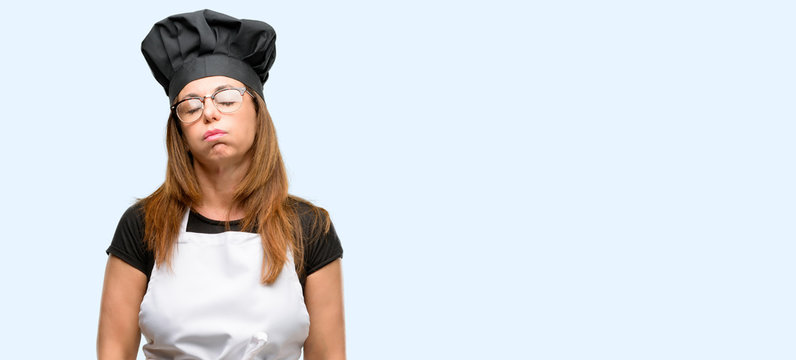 Middle age cook woman wearing chef apron with sleepy expression, being overworked and tired isolated blue background