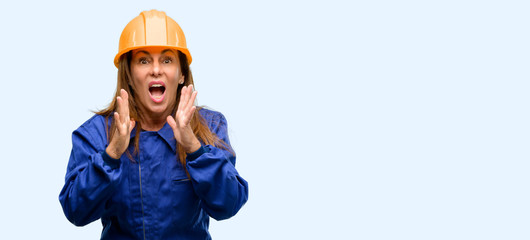 Engineer construction worker woman stressful keeping hands on head, terrified in panic, shouting isolated blue background