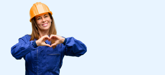 Engineer construction worker woman happy showing love with hands in heart shape expressing healthy and marriage symbol isolated blue background