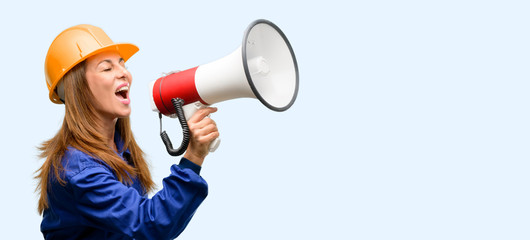 Engineer construction worker woman communicates shouting loud holding a megaphone, expressing success and positive concept, idea for marketing or sales isolated blue background