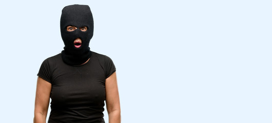 Burglar terrorist woman wearing balaclava ski mask scared in shock, expressing panic and fear isolated blue background