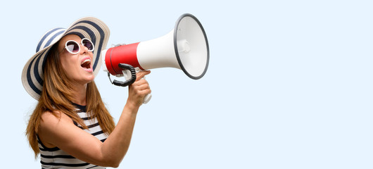Middle age cool woman wearing summer hat and sunglasses communicates shouting loud holding a megaphone, expressing success and positive concept, idea for marketing or sales isolated blue background