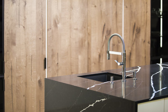 Kitchen faucet, modern kitchen in loft style, black marble table, wooden luxury kitchen