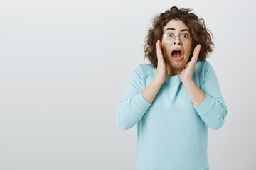 Oy my gosh, it is disgusting. Studio portrait of shocked and terrified attractive curly-haired brunette in stylish glasses, screaming from antipathy and shock, holding palms near mouth over gray wall