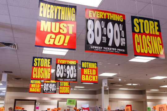 Store Closing and huge discount signs displayed at a going out of business sale III