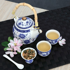 Japanese genmaicha fujiyama tea with oriental teapot, dried leaves, cups and spring  blossom on black mat, bamboo and slate background.