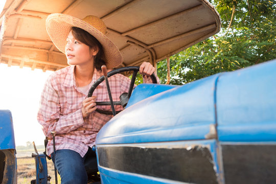 Portrait of smiling young asia woman on tractor in rice field