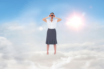 Shocked elegant businesswoman looking through binoculars against blue sky with white clouds