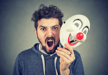 angry screaming man holding a clown mask