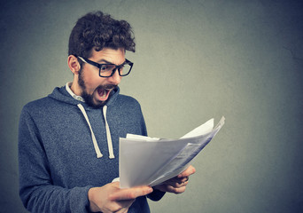 Angry stressed screaming man looking at documents papers