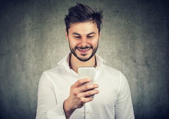 Happy guy watching smartphone