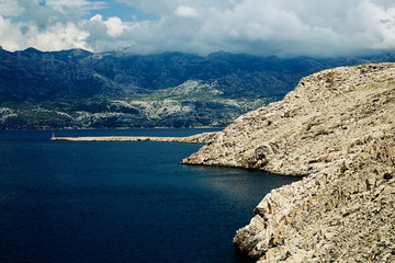 Rocky coast of the central part of Croatia. White clouds in the sky and blue sea.